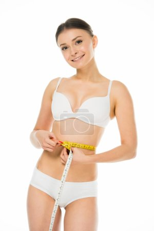 Photo for Happy slim woman measuring waist with centimeter isolated on white - Royalty Free Image