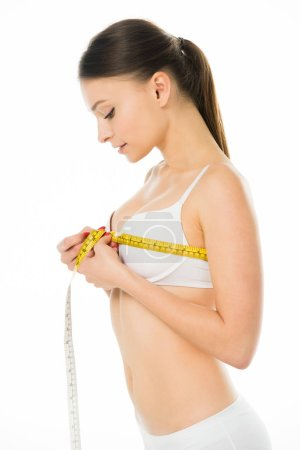 Photo for Slim woman in underwear measuring bust with centimeter isolated on white - Royalty Free Image