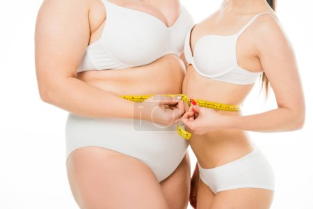 Photo for Cropped view of body positive overweight woman and slim woman holding measuring tape together isolated on white - Royalty Free Image