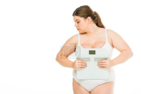 Photo for Upset young overweight woman in underwear holding scales and looking away isolated on white, lose weight concept - Royalty Free Image