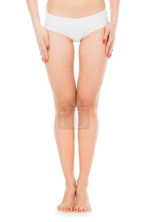 Photo pour Vue recadrée de femme mince posant avec les mains sur les jambes isolées sur blanc - image libre de droit