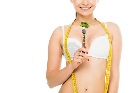 Photo for Cropped view of happy slim woman with measuring tape holding fork with green spinach leaves isolated on white, dieting concept - Royalty Free Image