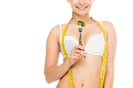 Foto de Vista recortada de la feliz mujer delgada con medición cinta sujetando la horquilla con hojas de espinaca verde aislados en blanco, dieta concepto - Imagen libre de derechos