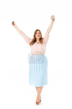 Foto de Feliz elegante más tamaño mujer sosteniendo donas dulces por encima de la cabeza aislado en blanco - Imagen libre de derechos