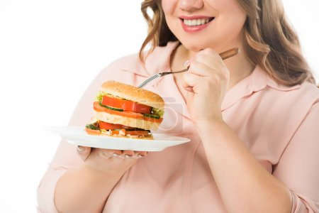 Photo for Cropped view of smiling woman eating tasty burger from plate with fork isolated on white - Royalty Free Image