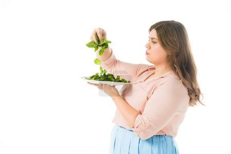Foto de Vista lateral de la mujer con sobrepeso espinacas frescas verdes hojas sobre placa aislada en blanco - Imagen libre de derechos