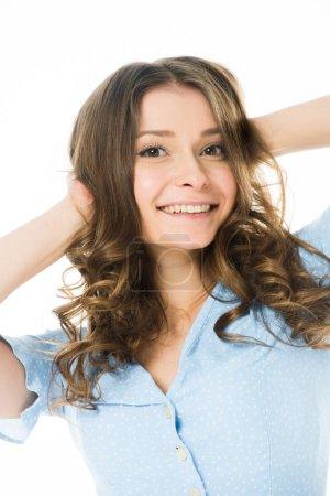 portrait de jolie fille souriante posant avec les mains sur la tête isolée sur blanc