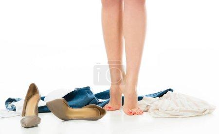 Photo pour Vue recadrée de femme debout sur la pointe des pieds avec des vêtements éparpillés autour de - image libre de droit