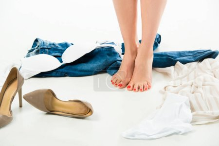 Photo for Partial view of woman standing on tiptoe with scattered clothes around - Royalty Free Image