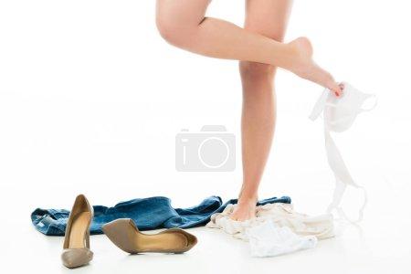 Photo pour Vue recadrée de femme tenant soutien-gorge à pied avec des vêtements éparpillés autour de - image libre de droit