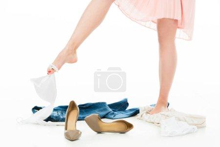 Photo pour Vue partielle de la femme tenant le soutien-gorge sur pied avec vêtements éparpillés autour de - image libre de droit