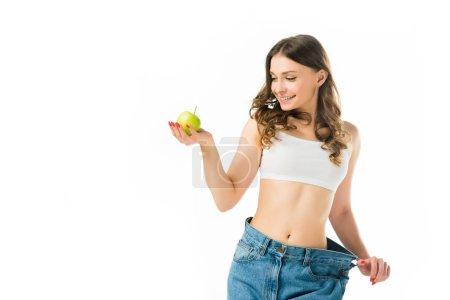 Photo pour Heureux mince jeune femme en gros jeans tenant pomme verte isolé sur blanc - image libre de droit