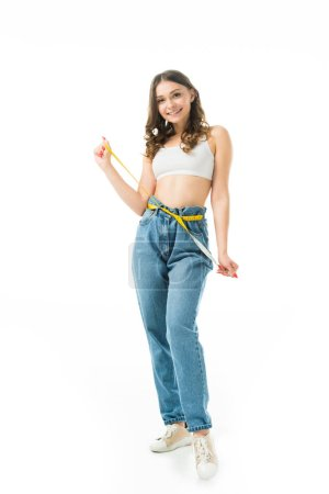 Photo for Smiling slim girl holding measuring tape on big jeans isolated on white, lose weight concept - Royalty Free Image