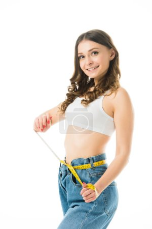 Photo for Cheerful woman holding measuring tape on big jeans isolated on white, lose weight concept - Royalty Free Image