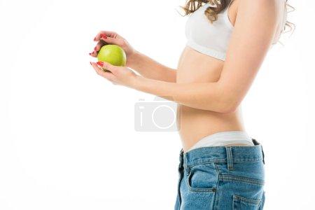 Photo pour Vue recadrée mince jeune femme en gros jeans tenant une pomme verte isolée sur blanc - image libre de droit