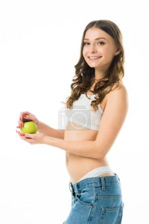 Photo pour Vue latérale du sourire mince jeune femme en gros jeans tenant la pomme verte isolé sur blanc - image libre de droit