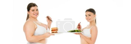 Photo for Overweight smiling woman in underwear holding burger on plate while slim happy woman eating green spinach leaves isolated on white - Royalty Free Image