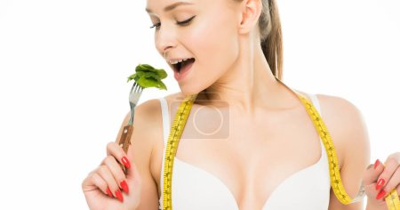 Photo for Beautiful woman with measuring tape eating green spinach leaves isolated on white, dieting concept - Royalty Free Image