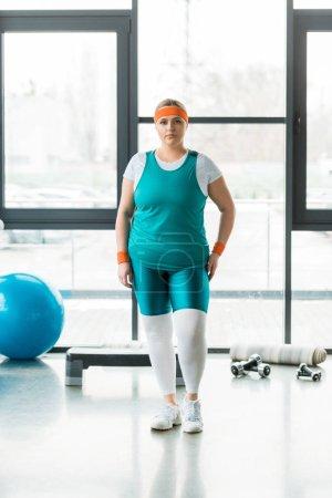 Photo pour Femme en surpoids debout dans les vêtements de sport près de ballon de remise en forme et haltères - image libre de droit
