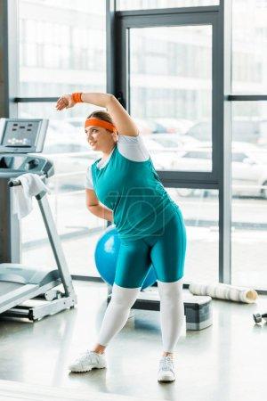 Photo pour Femme en surpoids joyeuse exerçant dans les vêtements de sport en salle de gym - image libre de droit