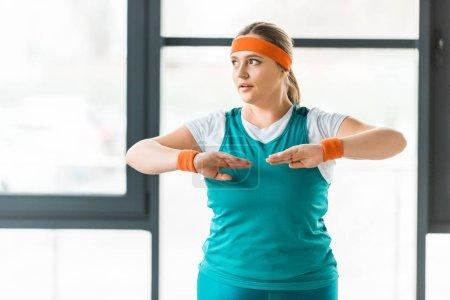 Photo pour Attrayante femme en surpoids faisant de l'exercice dans les vêtements de sport dans la salle de gym - image libre de droit