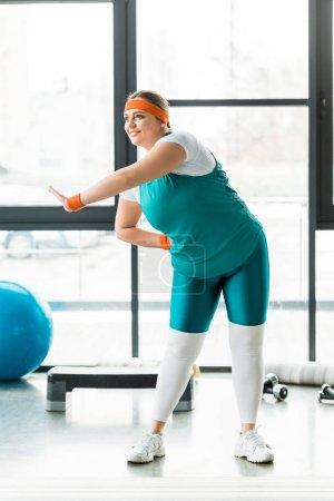 Photo pour Femme en surpoids joyeuse formation sportswear en salle de gym - image libre de droit