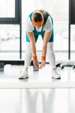 Photo pour Femme en surpoids qui s'étend en sportswear près de tapis fitness - image libre de droit
