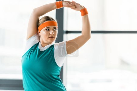 Photo for Overweight woman stretching while standing in sportswear in gym - Royalty Free Image