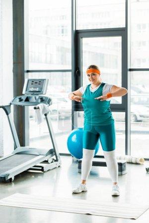 Photo pour Femme en surpoids qui s'étend tout en restant dans les vêtements de sport près de tapis fitness - image libre de droit