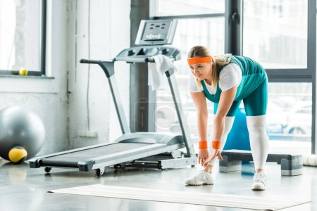 Photo for Overweight woman stretching near fitness mat and treadmill in gym - Royalty Free Image
