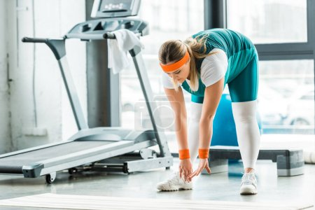 Photo for Concentrated overweight woman stretching near fitness mat and treadmill in gym - Royalty Free Image