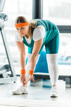 Photo pour Axé sur la femme en surpoids qui s'étend près de tapis de fitness dans la salle de gym - image libre de droit