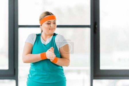 Photo pour Femme en surpoids debout dans les vêtements de sport et le réchauffement des mains - image libre de droit