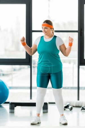 Photo for Smiling overweight woman training in sportswear in gym - Royalty Free Image