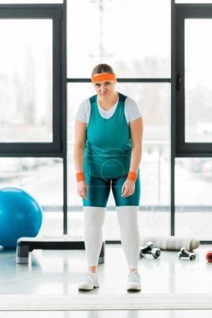 Photo pour Bouleversé femme en surpoids debout dans les vêtements de sport dans la salle de gym - image libre de droit