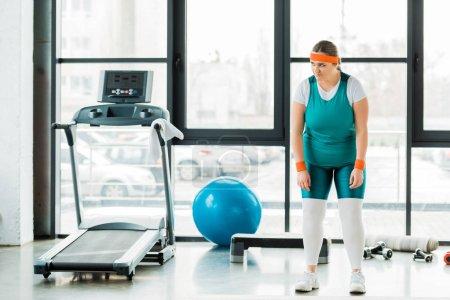 Photo pour Bouleversé femme en surpoids debout dans les vêtements de sport près de balle de fitness et tapis roulant - image libre de droit