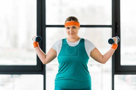 Photo pour Gaie femme en surpoids séance d'entraînement en vêtements de sport avec haltères - image libre de droit
