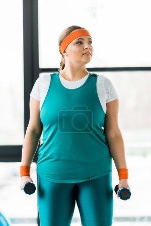Photo pour Workouting femme en surpoids songeur sportswear avec haltères - image libre de droit