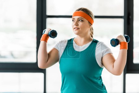 Photo for Cheerful overweight woman workouting with dumbbells in gym - Royalty Free Image