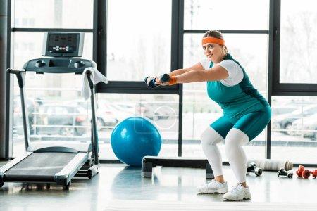 Photo pour Gaie femme plus la taille de l'exercice avec haltères près du tapis roulant - image libre de droit
