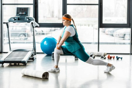 Photo for Confident plus size woman in sportswear stretching near fitness mat and treadmill - Royalty Free Image