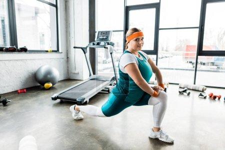 Photo pour Heureux plus la taille fille en vêtements de sport étirement dans la salle de gym - image libre de droit