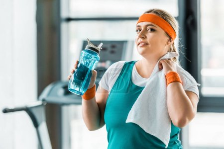 Photo for Exhausted plus size girl holding bottle with water and towel in gym - Royalty Free Image