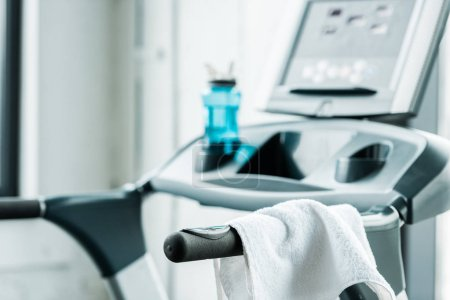 selective focus of white towel hanging on modern treadmill in gym