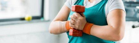 Photo pour Vue recadrée de la fille en surpoids tenant haltère dans la salle de gym - image libre de droit