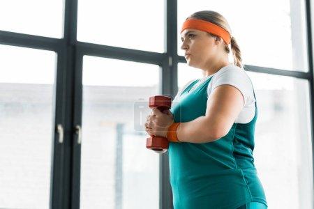 Photo pour Confiance fille en surpoids tenant haltère dans la salle de gym - image libre de droit