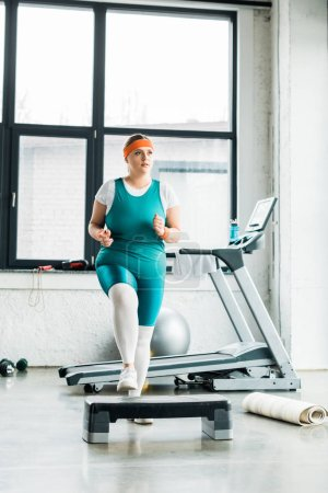 Photo for Plus size woman exercising on step platform near fitness mat in gym - Royalty Free Image