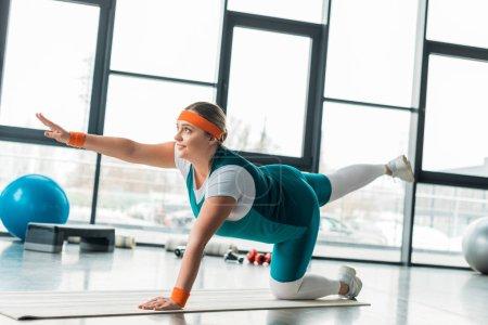 cheerful plus size girl exercising on fitness mat near sport equipment
