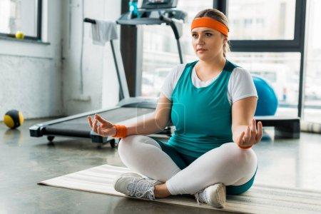 Photo pour Axé plus femme taille assise sur tapis de fitness près de matériel de sport avec jambes croisées - image libre de droit