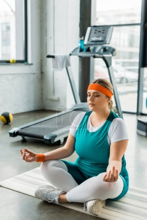 Photo for Plus size girl sitting on fitness mat near sport equipment with crossed legs and closed eyes - Royalty Free Image